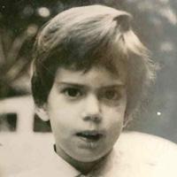 Foto em preto e branco de Bebel quando criança. Ela olha para a foto e tem cabelos curtos e franja que cobre a testa.