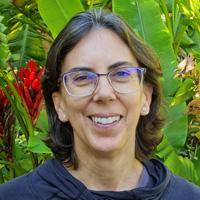 Foto de Bebel Barros, uma mulher branca de cabelos curtos. Ela sorri para a foto, usa óculos e está ao ar livre, em ambiente com plantas.