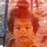 Foto antiga de Bela Gil quando criança. Ela tem o cabelo preso num coque.