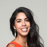 Foto de Bela Gil, uma mulher negra, com cabelos longos e ondulados. Ela sorri pra foto e usa um brinco prata e blusa laranja.