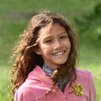 Foto de Catarina Lorenzo na infância. Ao ar livre, ela sorri para a foto e usa um casaco rosa.
