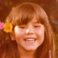 Foto de Claudia na infância. Em seus cabelos lisos e com franja, estão colocadas, no canto esquerdo, duas flores, uma rosa e outra amarela. Ela sorri para a foto.