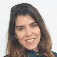 Foto de Claudia Vidigal, uma mulher branca com cabelos lisos e castanhos. Ela sorri para a foto e usa uma blusa azul.