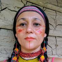 Foto de Cristine Takuá, uma mulher indígena, com cabelos lisos e trançados. Ela tem pinturas indígenas, feitas em seu rosto com a cor vermelha, e usa brincos, colares e uma tiara, todos com muitas cores.