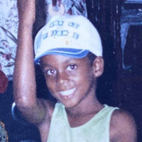 Foto de Danilo Farias quando criança. Ele sorri para a foto e usa um boné branco e azul com uma regata branca.