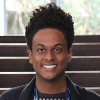 Foto de Danilo Farias, um homem negro de cabelo crespo. Ele sorri para a foto.