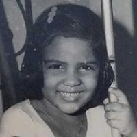 Foto em preto e branco de Eliane Moreira quando criança. Ela sorri para a foto e tem algumas mechas do cabelo curto presas por uma presilha.