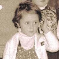 Foto antiga de Fernanda quando criança. Ela usa um casaco claro e blusa estampada, seus cabelos são claros e curtos.