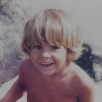 Foto de Gabri quando crianças, com cabelos loiros em um corte tigelinha. Ele sorri para a foto.