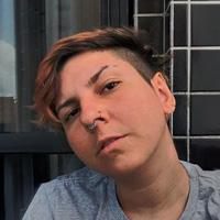 Foto de Gabri Baesse, uma pessoa não binária, com cabelos curtos e raspados de um lado.