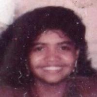 Foto antiga de Gaby Amarantos quando criança. Ela está com os cabelos soltos e sorri para a foto.