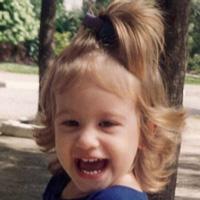 Foto de Julia Berro quando criança. Ela sorri para a foto e seus cabelos loiros têm algumas mechas presas no alto da cabeça.