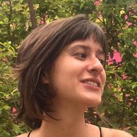 Foto de Julia Berro, uma mulher branca de cabelos curtos e com franja.