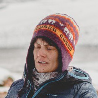 Foto de Juliana Tozzi, uma mulher branca usando touca e casacos. Ela está ao ar livre, em uma paisagem com neve.
