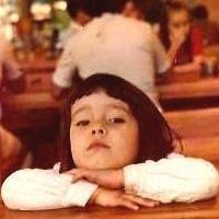 Foto de Kiara Terra, quando criança, com cabelos lisos e franja. Ela olha séria para a foto, com a cabeça apoiada nos braços cruzados sobre uma mesa.