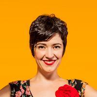 Foto de Kiara Terra, uma mulher branca de cabelos curtos. Ela sorri para a foto e tem uma flor vermelha presa em sua blusa.