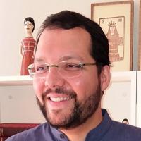 Foto de Levindo Carvalho, um homem branco e com barba. Ele sorri para a foto e usa óculos.