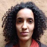 Foto de Lila Barbosa, uma mulher de cabelos escuros e cacheados.