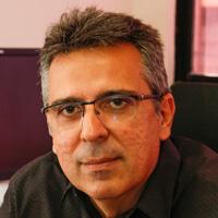 Foto de Luiz Alberto Sabóia, um homem branco de cabelos curtos e grisalhos. Ela usa óculos e camisa preta.