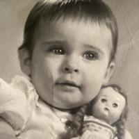 Foto em preto e branco de Marilene quando criança. Ela usa roupas claras e está abraçada com uma boneca.