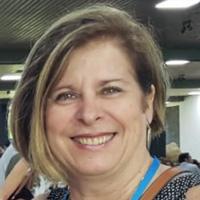 Foto de Marilene Proença, uma mulher branca de cabelos curtos e mechas loiras. Ela sorri para a foto.