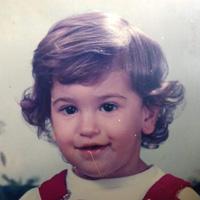 Foto de Maurício Guetta quando criança. Ele sorri para a foto com cabelos claros e ondulados nas pontas.