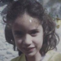 Foto antiga de Paula Mendonça na infância, com cabelos curtos e sorriso discreto.