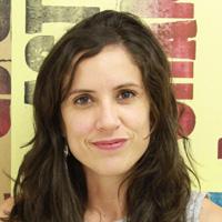 Foto de Paula Mendonça, uma mulher branca de cabelos longos e castanhos.