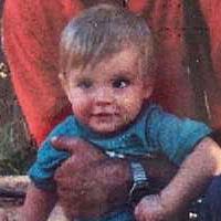 Foto de Pedro quando criança. Ele tem cabelos claros e usa uma blusa azul.