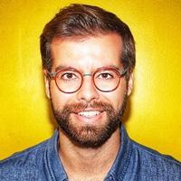 Foto de Pedro Hartung, um homem branco de cabelos castanhos claros e barba. Ele sorri para a foto, usa óculos e camisa azul.