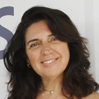 Foto de Regina Cavini, uma mulher de cabelos escuros e ondulados. Ela sorri para a foto e usa um colar com pequeno pingente.