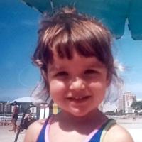 Foto de Júlia quando criança, na praia. Ela tem franja e sorri para a foto, usando um maiô azul.