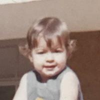 Foto de Sylvia na infância. Ela tem cabelos claros e curtos e usa um vestido azul.
