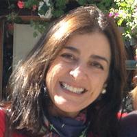 Foto de Sylvia Angelini, uma mulher branca de cabelos lisos e castanhos. Ela sorri pra foto e usa um lenço azul no pescoço.