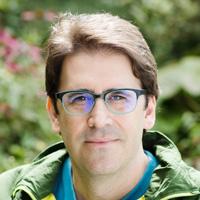 Foto de Tasso Azevedo, um homem branco com cabelos castanhos. Ele usa óculos, uma camiseta azul e casaco verde.