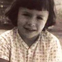 Foto antiga de Teresa Surita na infância. Ela olha pra foto, com cabelos curtos e franja, usando uma blusa com bolinhas.