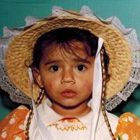 Foto de Thabata quando criança. Ela olha séria para a foto e usa um chapéu de palha, com trancinhas penduradas, típico de festas juninas.