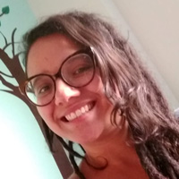Foto de Thabata dos Santos, uma mulher branca de cabelos ondulados e castanhos. Ela sorri para a foto e usa óculos.
