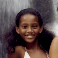 Foto de Taís Araújo na infância. Ela sorri para a foto e ao fundo é possível ver a queda d'água de uma cachoeira.