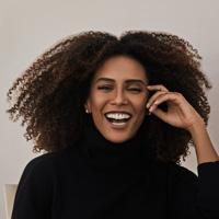 Foto de Taís Araújo, uma mulher negra de cabelos crespos. Ela sorri para a foto e usa uma blusa preta.
