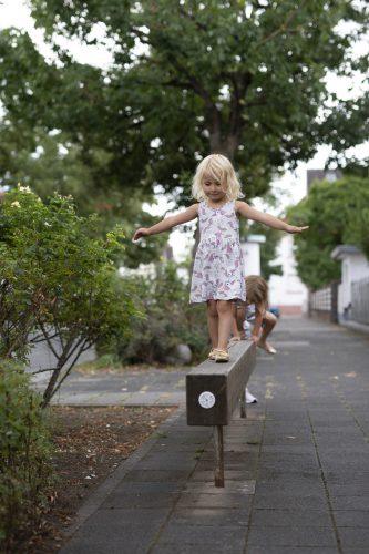 Criança se equilibrando em uma barra de madeira instalada em uma calçada. Ao fundo árvores e arbustos.