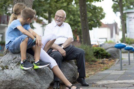 Bernhard Meyer, autor do livro Cidades para Brincar e Sentar, conversando com crianças, sentados sobre pedras em uma calçada na Alemanha.