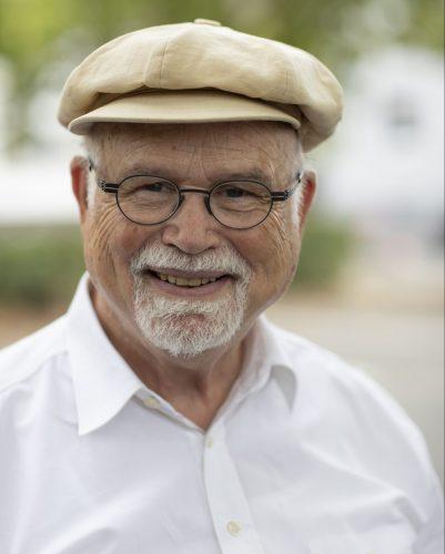 Foto do professor Bernhard Meyer, um homem branco de cabelos e barba grisalhos. Ele usa óculos, uma boina bege e uma camisa branca de botões.