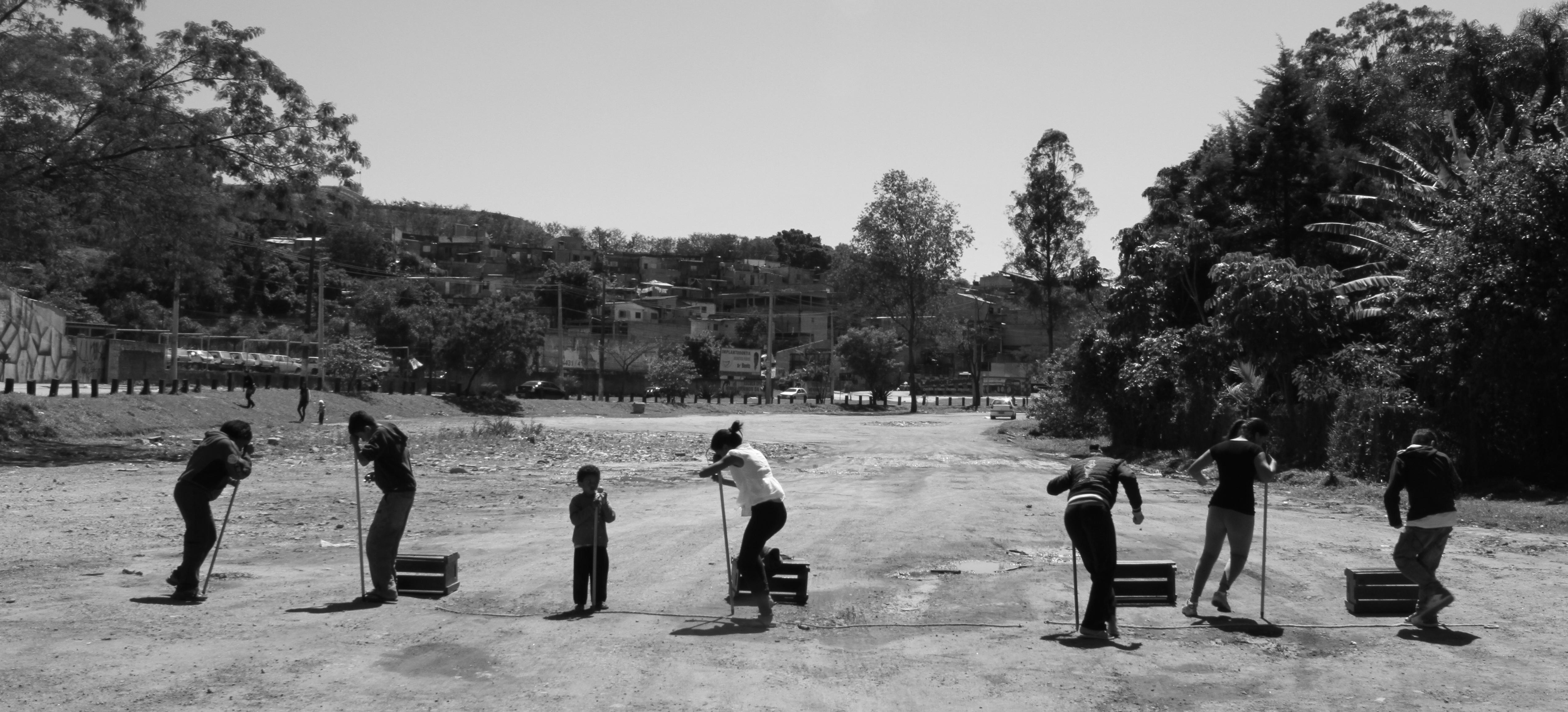 Foto em preto e branco de um grupo de crianças brincando, em um parque de terra, com alguns caixotes e pedaços de madeira. Ao fundo muitas árvores.
