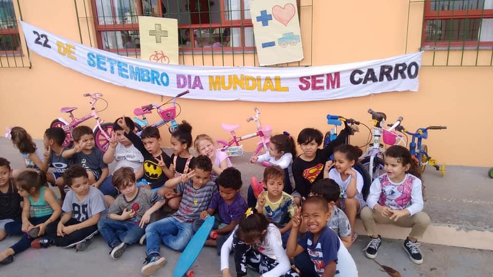 """Grupo de crianças está sentado com suas bicicletas em frente a uma casa. Atrás delas uma faixa escrita """"22 de setembro dia mundial sem carro""""."""