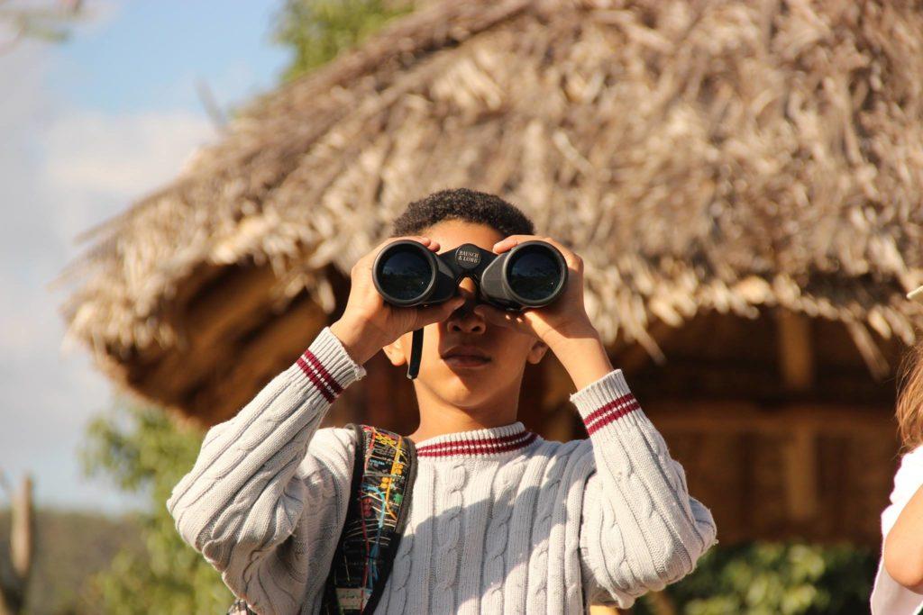 Garoto olha para frente através de um binóculos. Atrás dele uma cabana de palha e o céu azul.