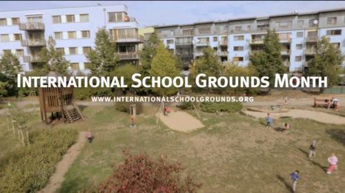 """Vista aérea de um pátio escolar gramado e arborizado com crianças brincando, ao fundo alguns prédios. Sobre a imagem está escrito em branco """"International School Grounds Month""""."""