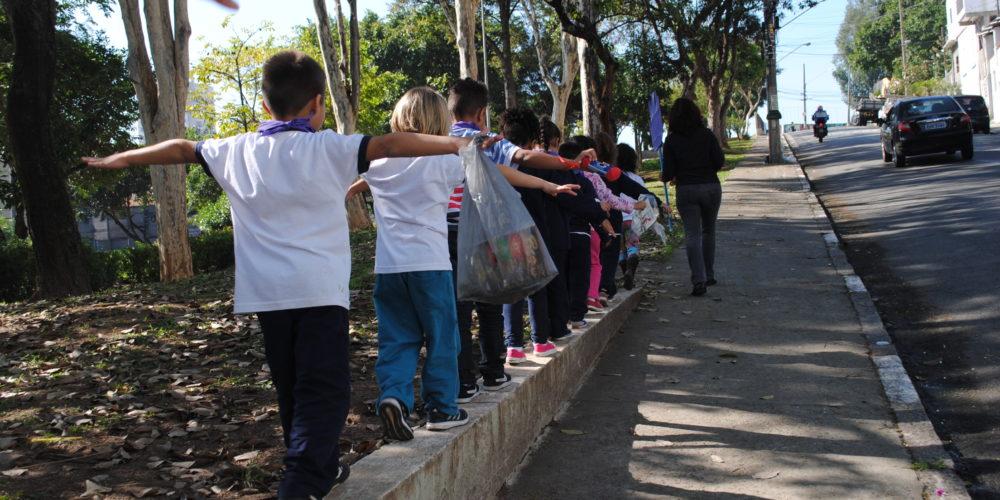 Grupo de crianças caminha sobre mureta na beira da calçada.