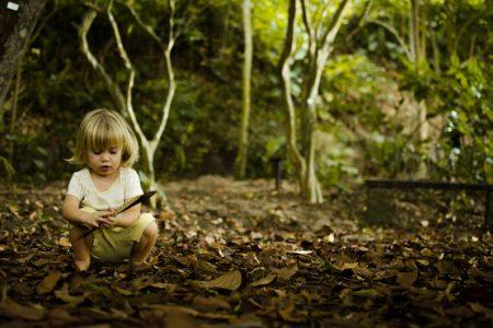 Criança está agachada em meio a folhas brincando com um galho.
