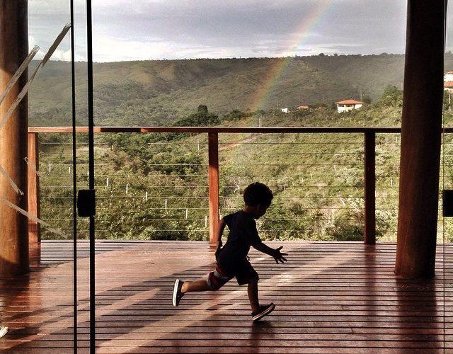 Menino corre em uma varanda. Atrás dele um vale cheio de árvores e um arco íris.